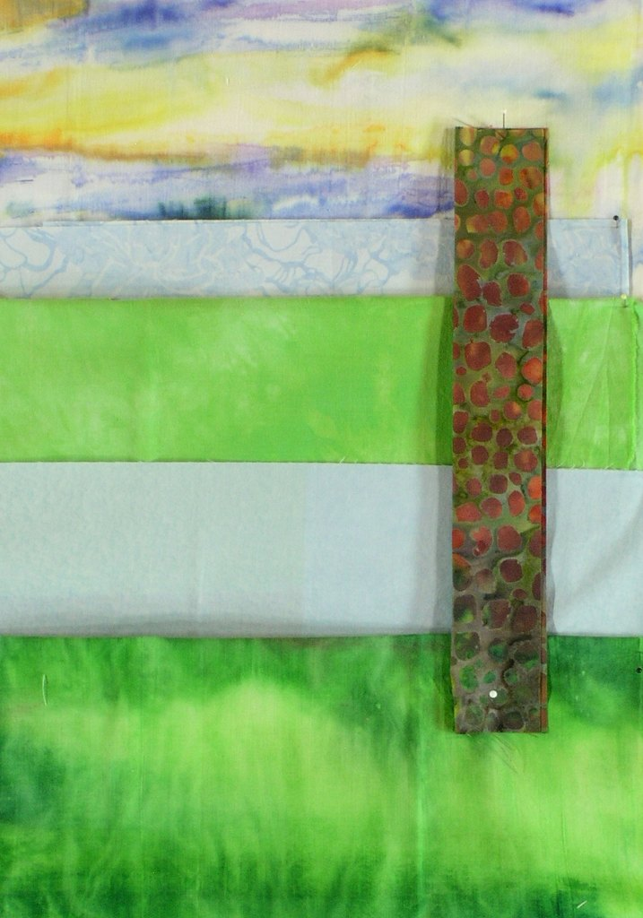 Fabric is stacked in an overlapping manner, starting with a hand dyed mottled green at the base and working up to a hand painted, dramatic sunrise. There is one thin vertical strip to indicate the tree that will be in the foreground.