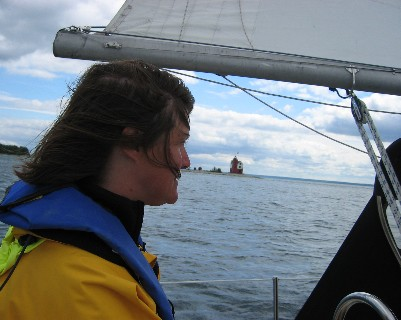 Photo: Lisa Borre at the helm sailing to Mackinaw City, Michigan. Credit: D.R. Barker.