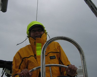"""Photo: Lisa Borre at helm of s/v """"About Time"""" on Lake Superior. Credit: D.R. Barker."""