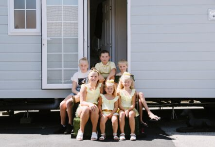 Picture of children sat on a step of a caravan