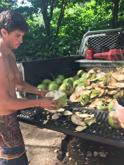 A man prepares a coconut at Ke'e Beach in Ha'ena State Park