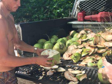 A man prepares a coconut at Ke'e Beach in Ha'ena State Park