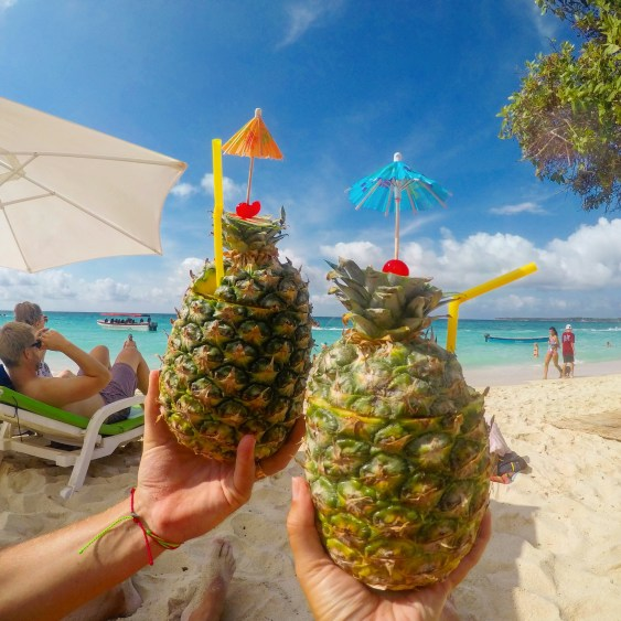 drinking pineapple pina coladas on playa blanca colombia