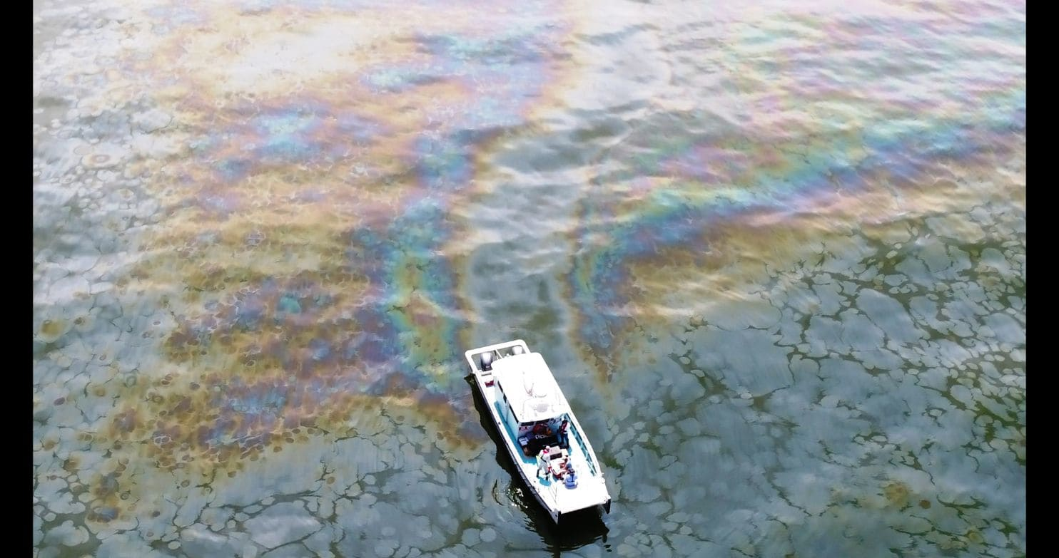 photo: boat in water reflecting oil spill colors.