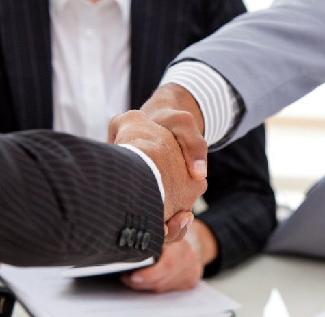 Close-up of businessmen closing a deal in a meeting