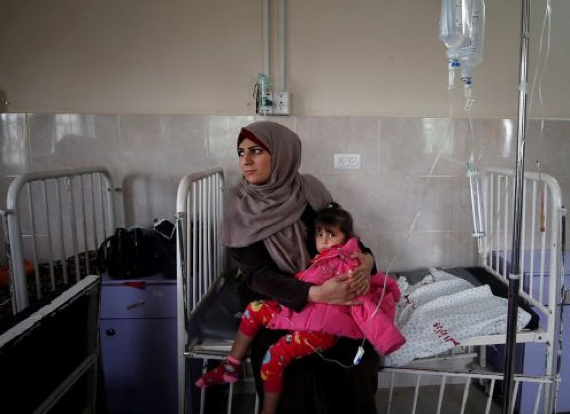 A sick Palestinian girl is held by her mother inside a room at the Durra hospital in Gaza City, February 6, 2018.