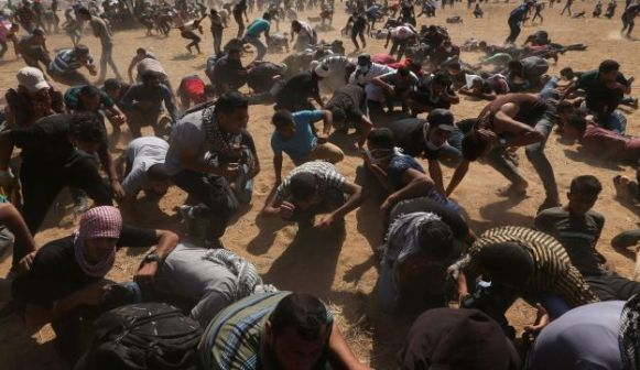 Palestinian demonstrators take cover from Israeli fire during a protest at the Israel-Gaza border in the southern Gaza Strip June 8, 2018.