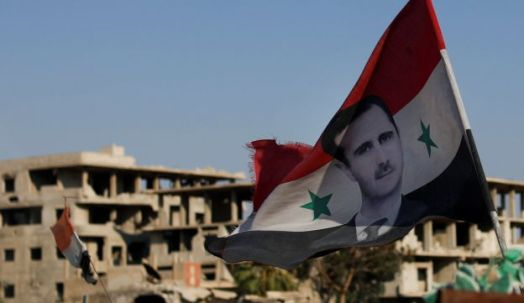 A Syrian national flag with the picture of the Syrian President Bashar Assad hangs at an army check point, in the town of Douma in eastern Ghouta, near the Syrian capital Damascus. July 15, 2018