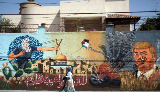 """Palestinian women walk next to a wall with graffiti showing U.S. President Donald Trump with a footprint on his face and Arabic that reads, """"For al-Quds (Jerusalem) and the right of return we resist,"""" in Gaza City, May 20, 2018."""