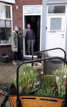 Jorien brengt een bloemetje aan een blije buur. Fotografie: Anneke Mensink van fotografencollectief In The Picture.