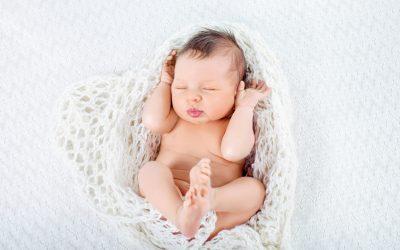 Sleeping newborn baby boy lies in a knite plaid