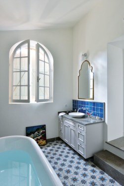 The master suite bathroom has blue and white floor tiles, which follow the same palette from the main bedroom.