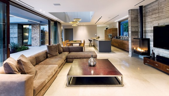 The open plan living space includes: lounge, dining room and kitchen, and opens onto the swimming pool via expansive glazed timber sliding doors.