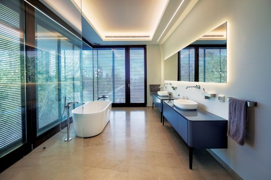 Filtered natural light enters the spacious main en suite bathroom through full height corner glazing. Indirect architectural lighting has been employed extensively throughout the home.
