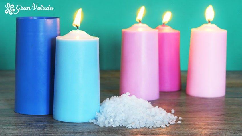 Imagen de 4 velas caseras de colores junto a un molde de velas y un poco de Cera con la que están fabricadas.