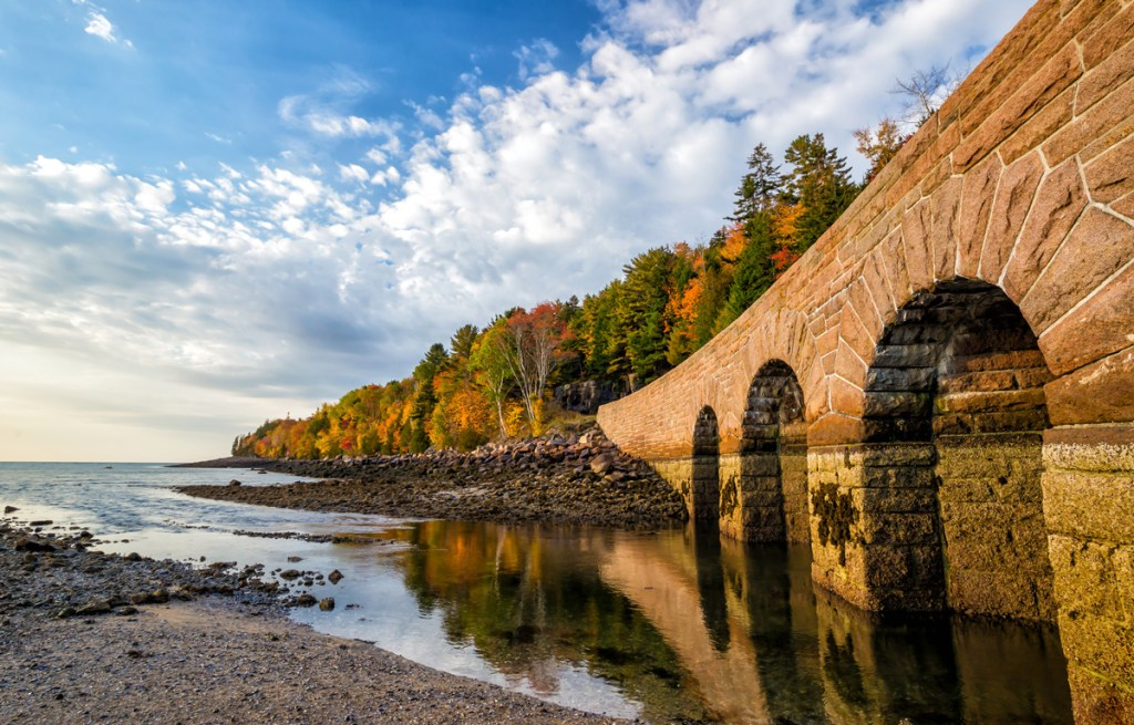 bridge reflected in water with fall foliage