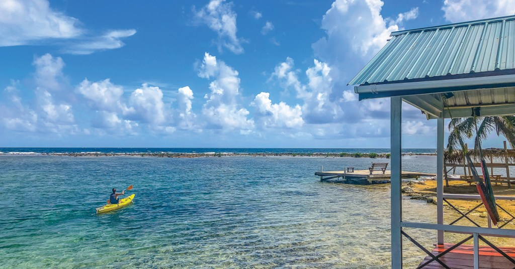 kayaker on the clear waters of tobacco caye
