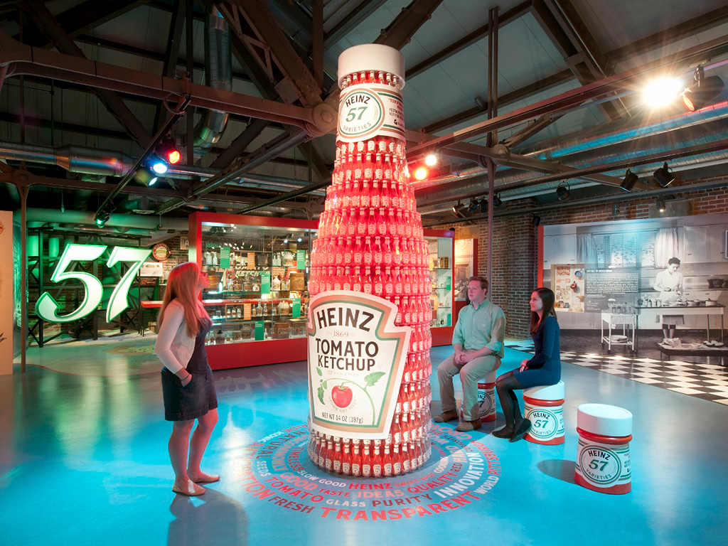 museum visitor stands next to an oversized ketchup bottle art installation