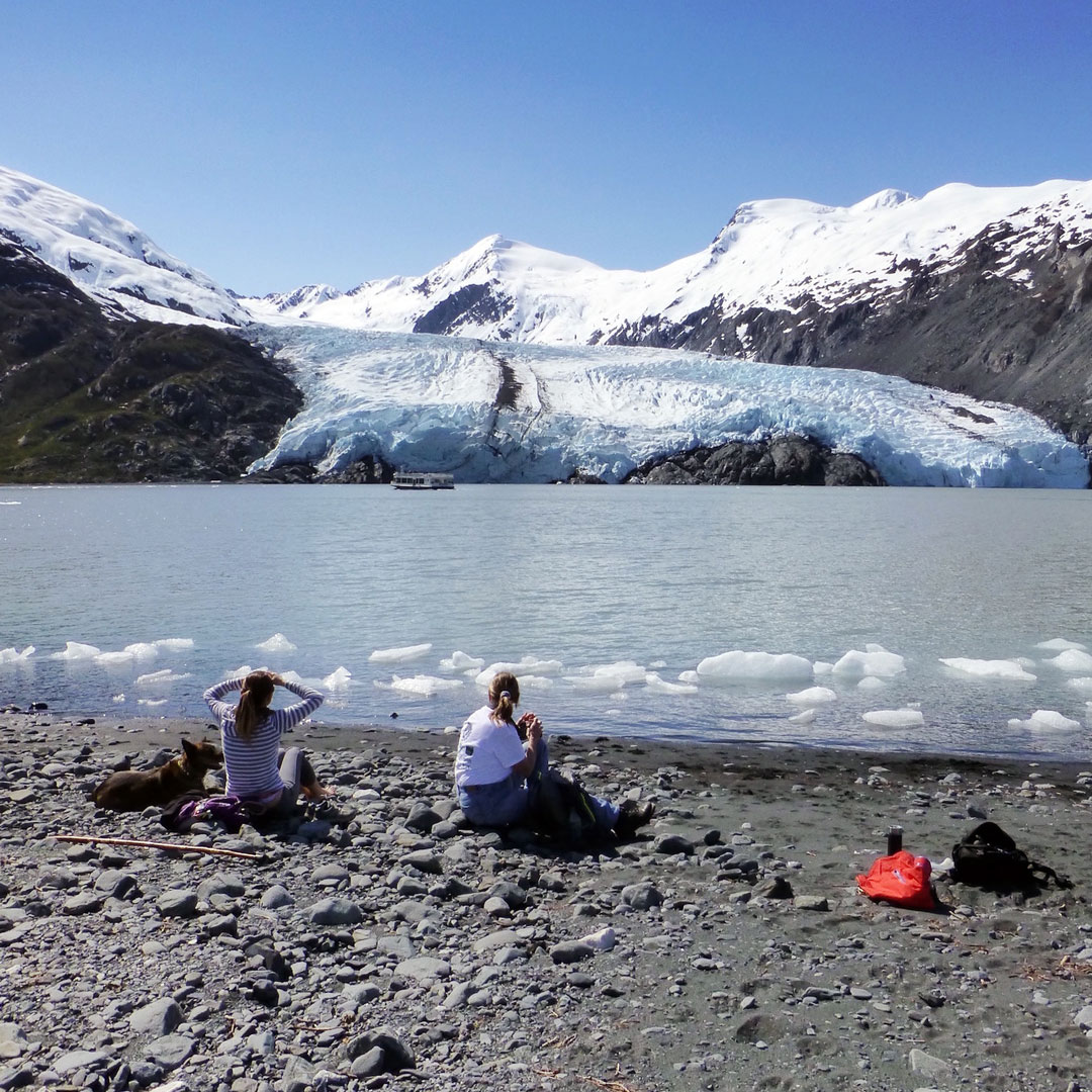 hikers on the beach near portage glacier in Alaska