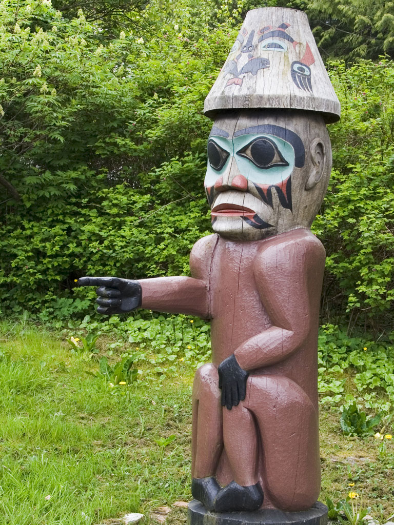 a totem pole figure pointing