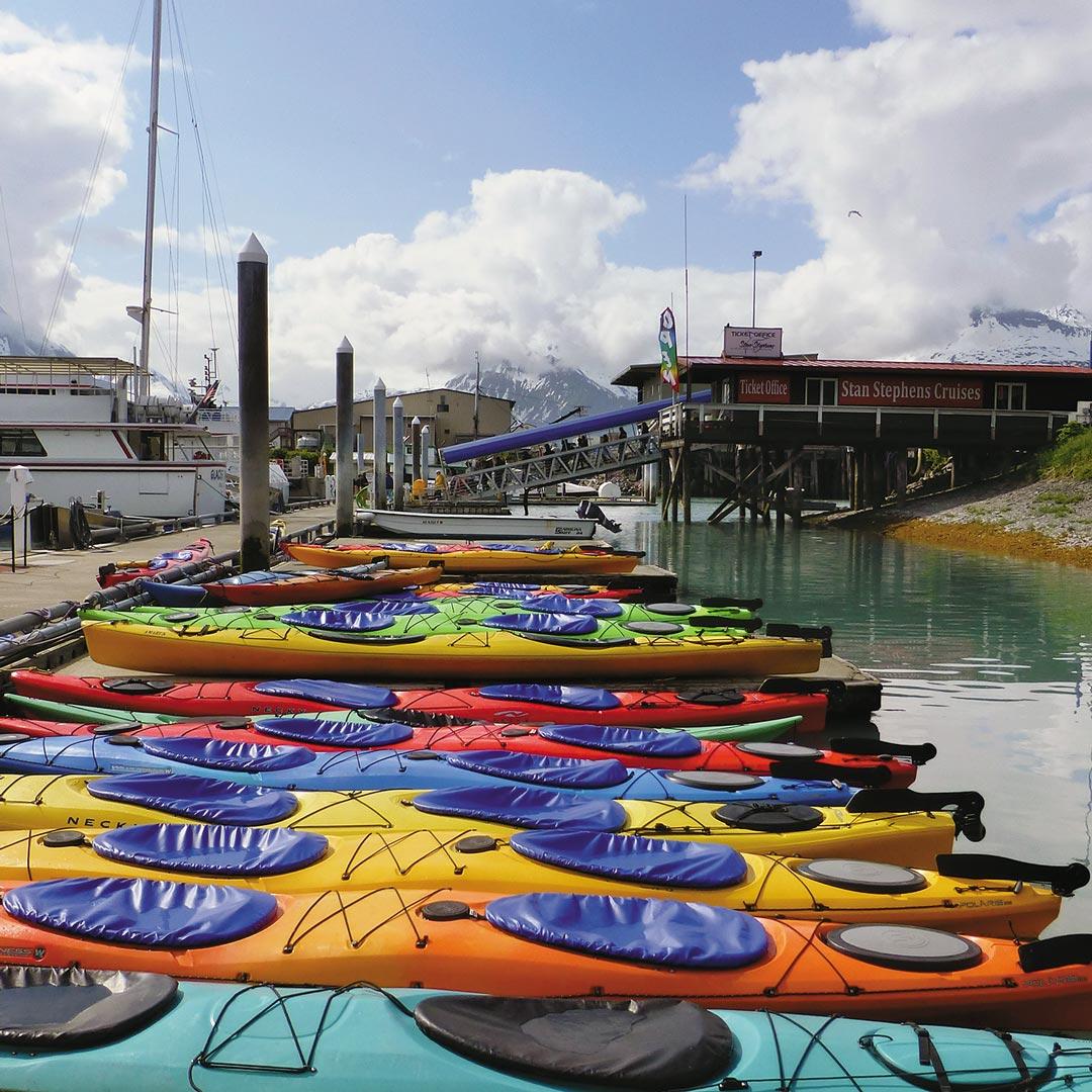 colorful row of kayaks in Valdez