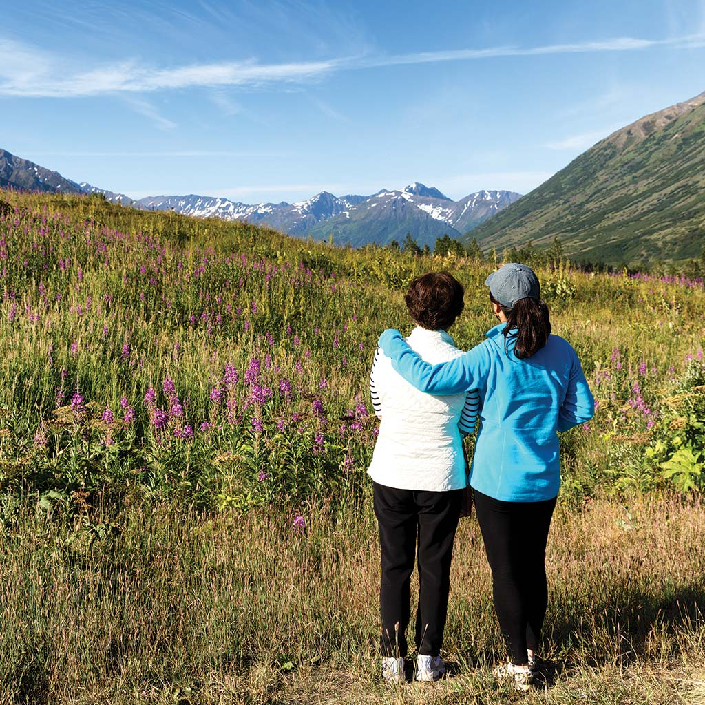 Two women stand together and admire the Denali landscape