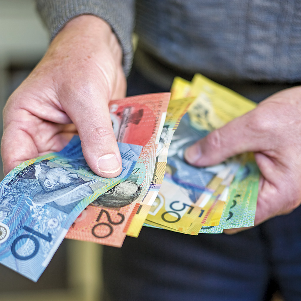 Hands sorting through Australian currency
