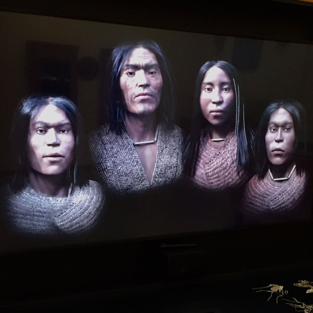 depiction of four indigenous people on a screen