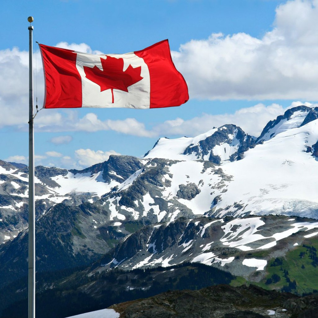 Canadian flag flying over snowy peaks in Whistler