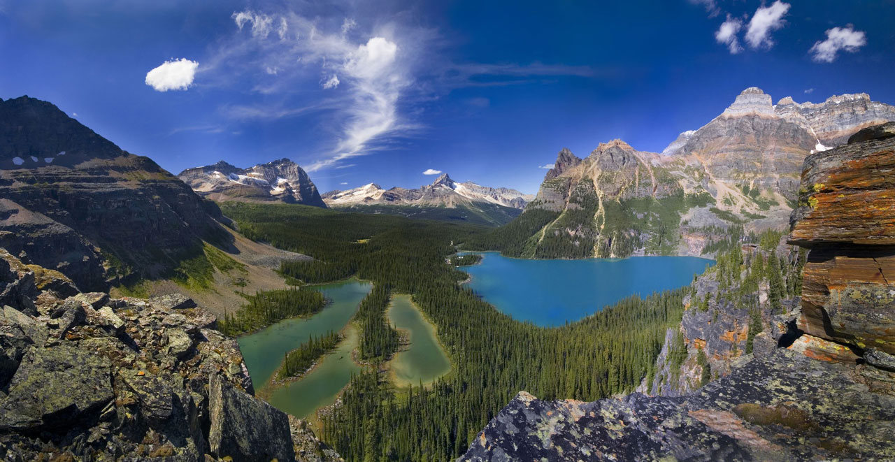 Panoramic view of an alpine lake surrounded by mountain peaks.