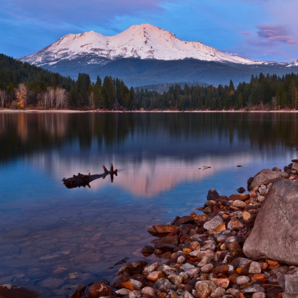 a mountain reflected in the water below at sunset