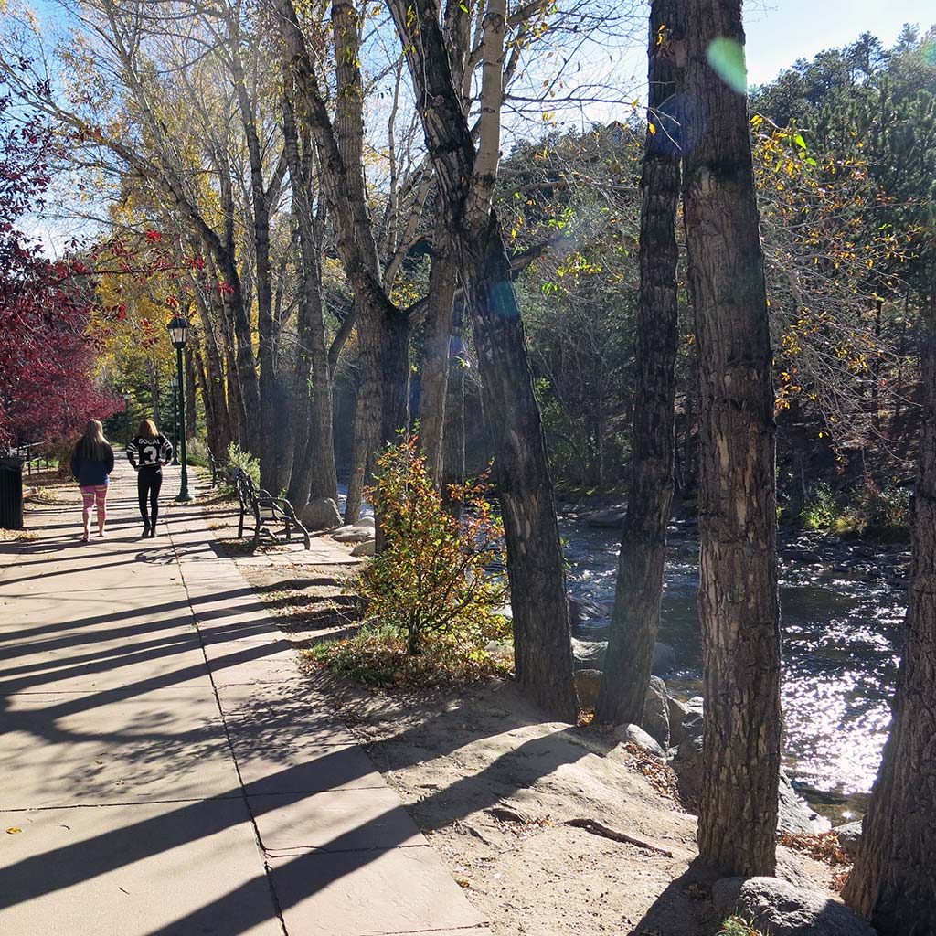 Pedestrians on a tree-lined paved path alongside the Fall River.