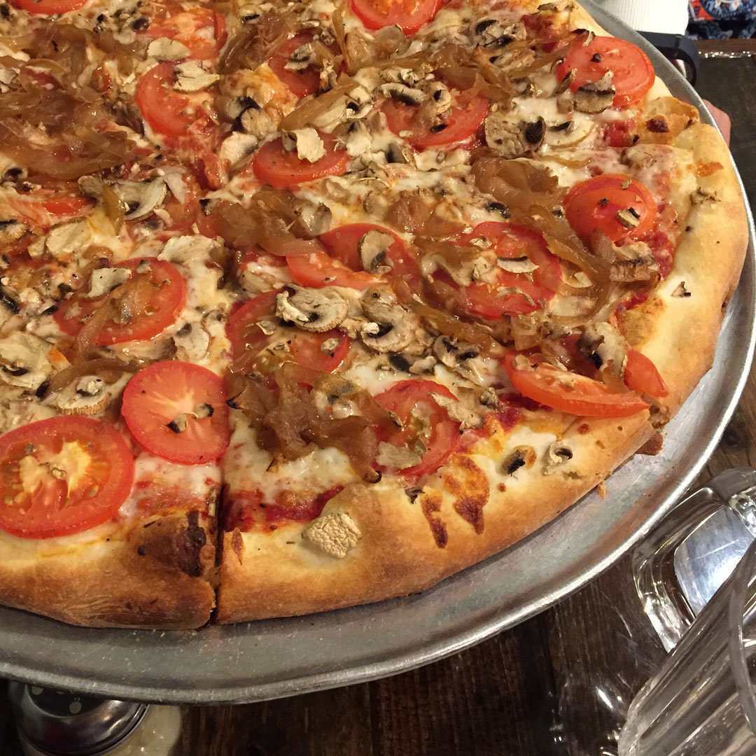 pizza topped with tomatoes mushrooms and carmelized onions