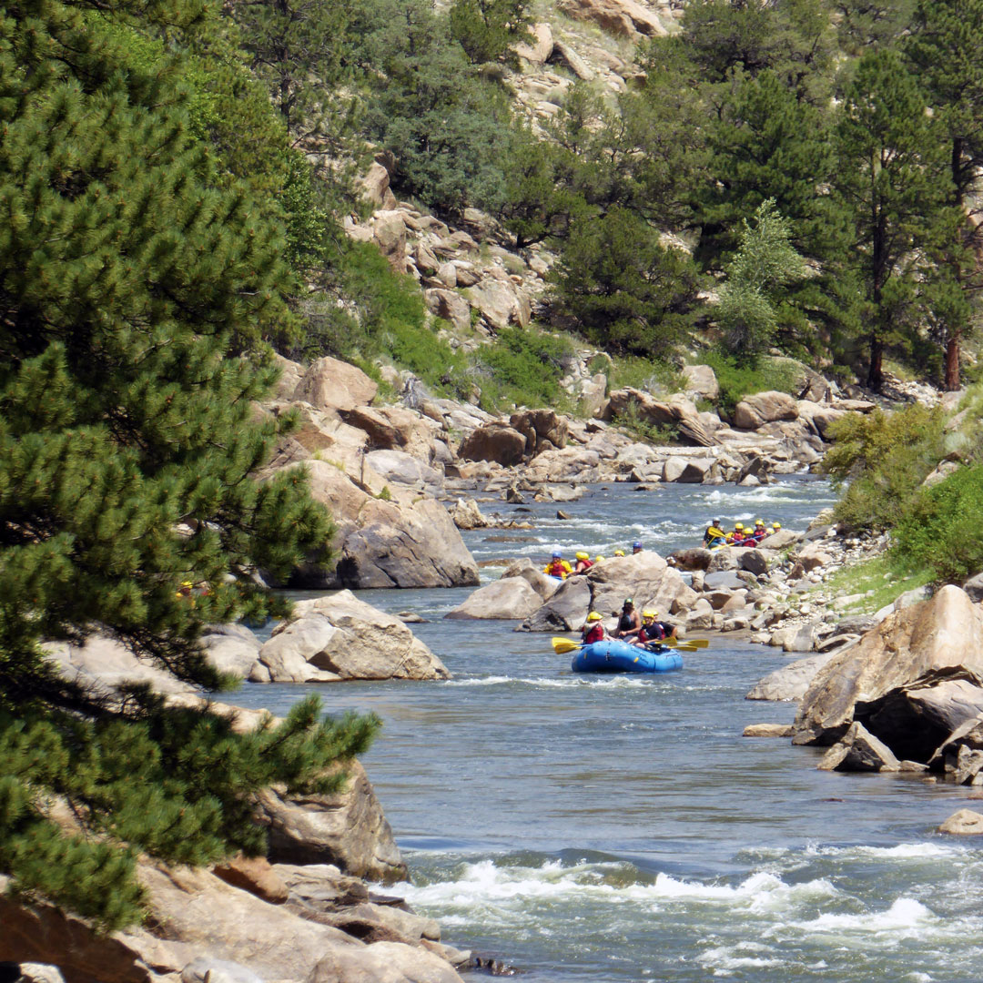 rafts full of people on the Roaring Fork river surrounded by rocks and trees