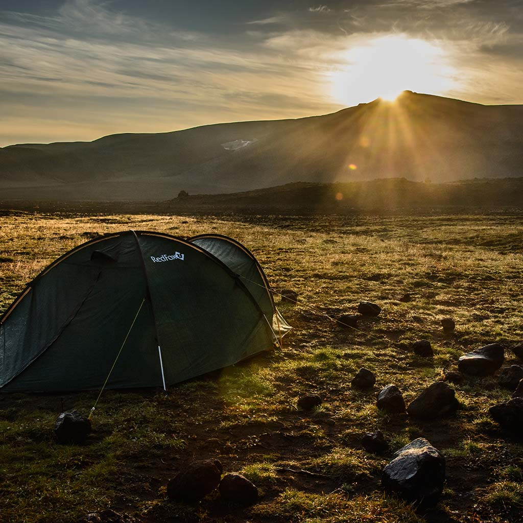 A tent in a field with the sun rising over a range of mountains.