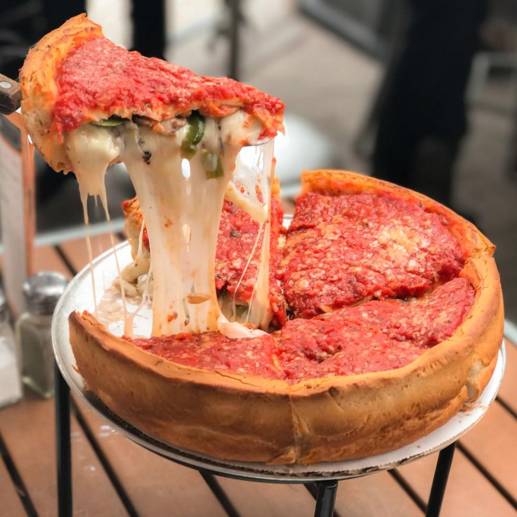 a slice being pulled from a deep dish pizza