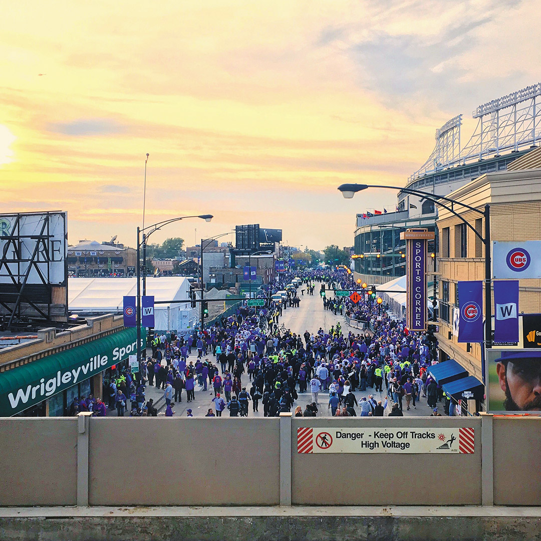 a Chicago street near Wrigley Field is filled with people at sunset