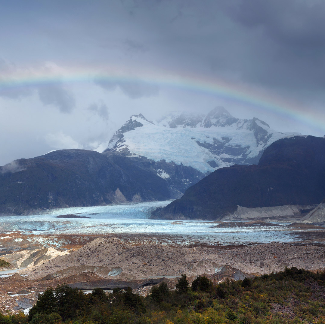 a rainbow spans over monte san valentin in chilean patagonia