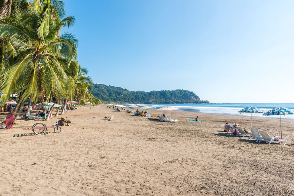 The broad sandy beach at Jaco, Costa Rica is studded with lounges.