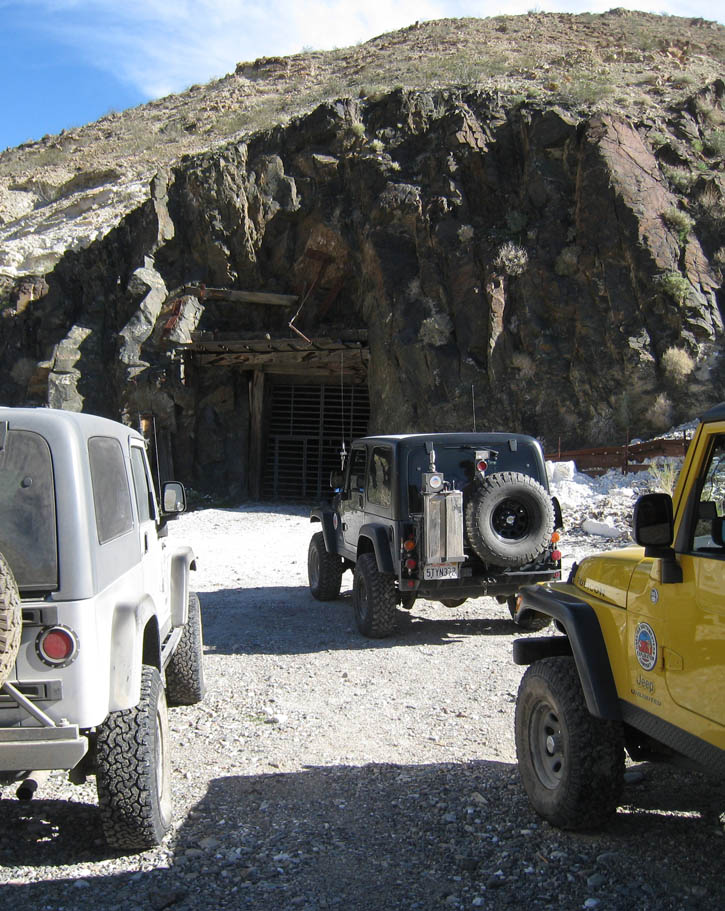 Jeeps parked at large mine entrance above Death Valley, California.