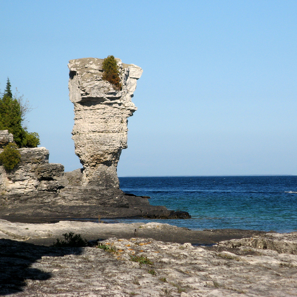A rocky island is pictured with a towering rock structure