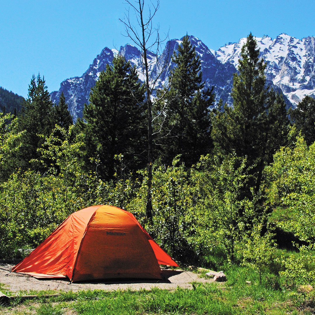 orange tent camping with a view of the Teton mountains