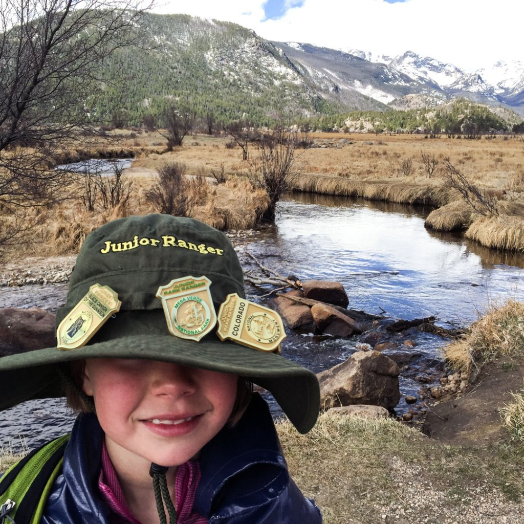 child with a large floppy hat covered in ranger badges