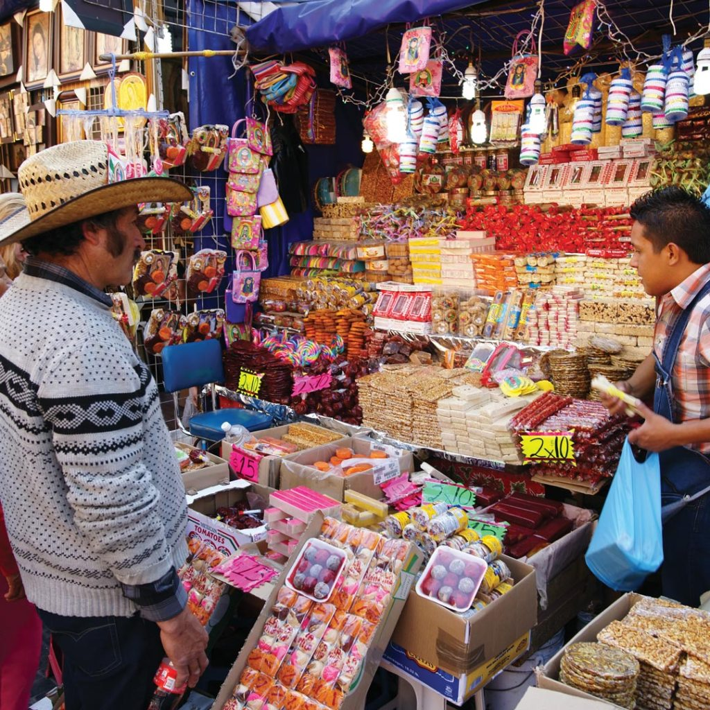 man wearing a hat while perusing items for sale in the mercado de la merced