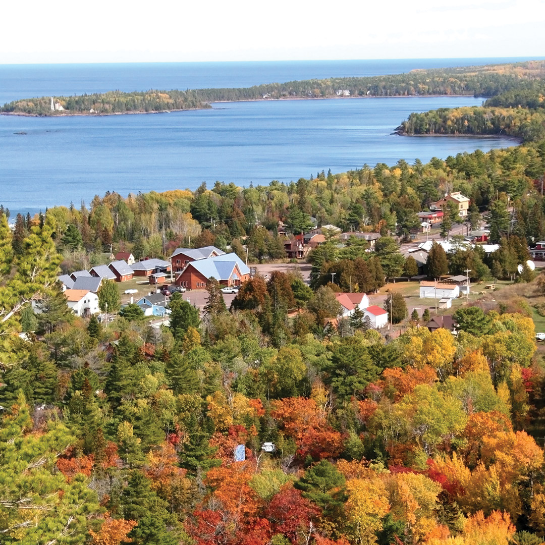 red, orange, and yellow trees surround the lake in Copper Harbor