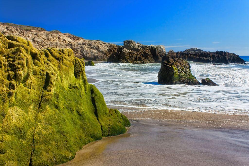 frothy ocean water against rocky coastline