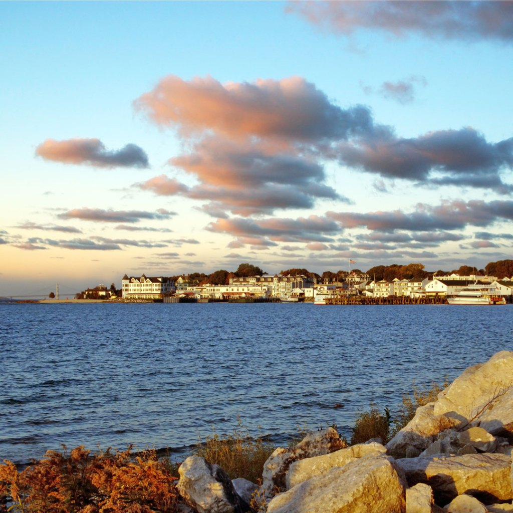 the sun sets over the lake surrounding Mackinac Island