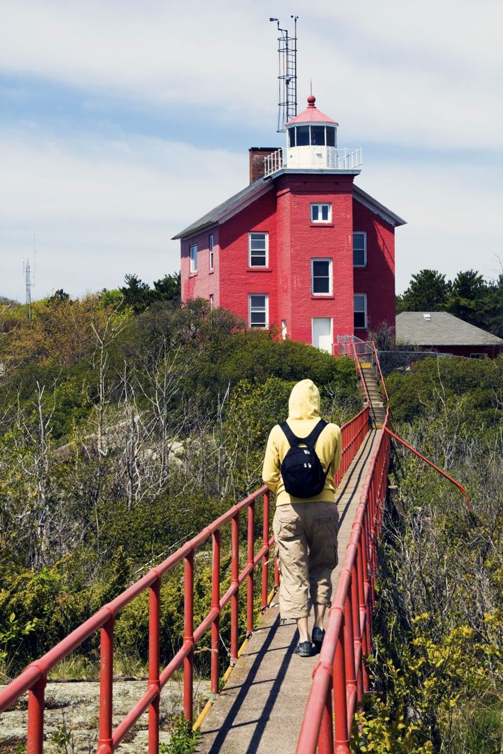 A traveler crosses a footbridge to the Marquette Harbor Lighthouse.