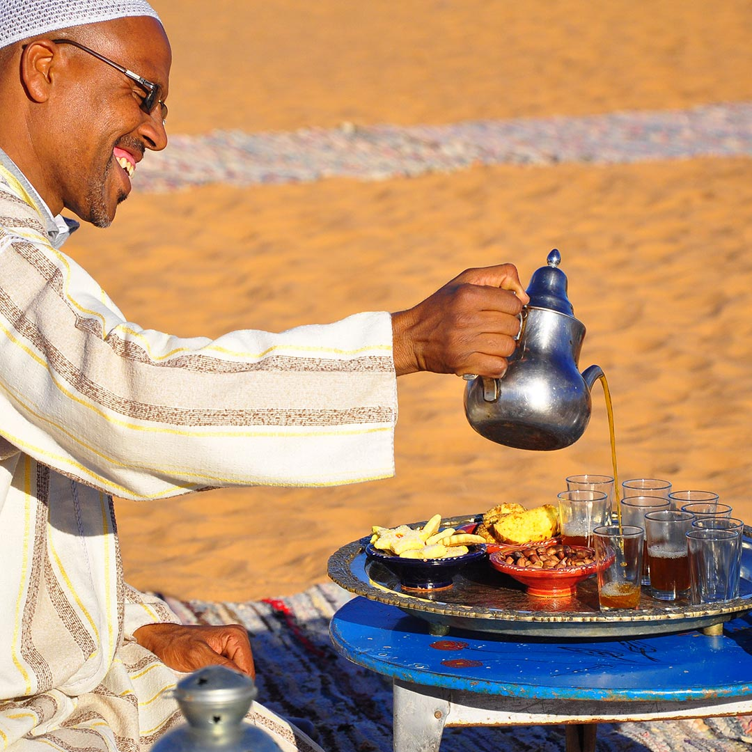 man pouring tea in the Moroccan desert