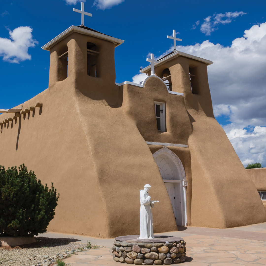 church in taos with a statue of a priest in front